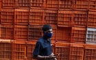 A man wearing a protective mask walks past baskets stacked at a flower market amidst the spread of the coronavirus disease (COVID-19), in Mumbai, India, October 20, 2020. REUTERS/Francis Mascarenhas/Files