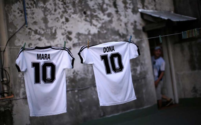 T-shirts with the names of Mara and Dona, twin daughters of Walter Gaston Rotundo, a devoted Diego Maradona fan that named his daughters after the football star, are seen on the clothesline at the family house, in Buenos Aires, Argentina, Nov 27, 2020. REUTERS