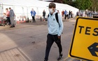 A man walks past people queueing outside a test centre, following an outbreak of the coronavirus disease (COVID-19), in Southend-on-sea, Britain Sept 17, 2020. REUTERS