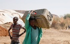 An Ethiopian refugee carries a suitcase at the Um Rakuba refugee camp which houses Ethiopian refugees fleeing the fighting in the Tigray region, on the Sudan-Ethiopia border, Sudan, November 28, 2020. REUTERS
