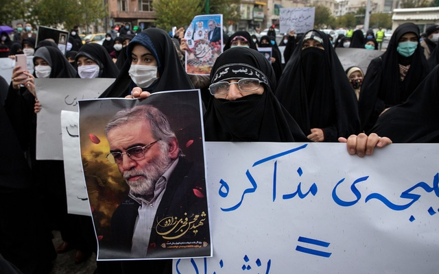 A protester holds an image of the Iranian nuclear scientist Mohsen Fakhrizadeh during a demonstration in Tehran on Saturday, Nov. 28, 2020, a day after Fakhrizadeh was killed. (Arash Khamooshi/The New York Times)