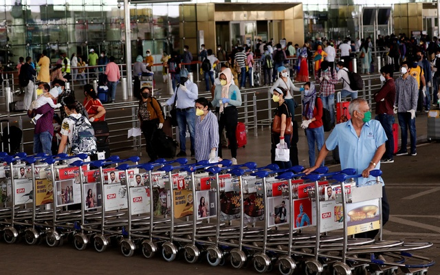 FILE PHOTO: An airport staff member pushes trolleys at the entrance of Mumbai's airport after the Indian government allowed domestic flight services to resume during an extended nationwide lockdown to slow the spread of the coronavirus disease (COVID-19), May 25, 2020. REUTERS