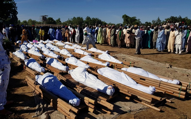 Men gather near dead bodies of people who were killed by militant attack, during a mass burial at Zabarmari, in the Jere local government area of Borno State, in northeast Nigeria, November 29, 2020. REUTERS/Ahmed Kingimi
