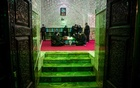 Mourners sit next to the coffin of Iranian nuclear scientist Mohsen Fakhrizadeh, during the burial ceremony at the shrine of Imamzadeh Saleh, in Tehran, Iran Nov 30, 2020. REUTERS