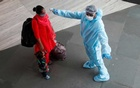 FILE PHOTO: A health worker in personal protective equipment (PPE) checks the temperature of a passenger at a railway station, amid the spread of the coronavirus disease (COVID-19), in Mumbai, India November 27, 2020. REUTERS/Francis Mascarenhas/File photo