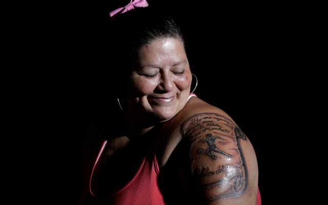 Cintia Veronica, a devoted Diego Maradona fan who has an image of Maradona tattooed on her arm, poses for a photo at her home in Buenos Aires, Argentina, November 29, 2020