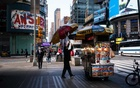 A food cart in Midtown Manhattan's Times Square area, Oct. 8, 2020. With the coronavirus keeping away the usual throngs of visitors to Times Square and surrounding Midtown, a faint fear stirs that the famous nexus could slip back to its 1970s self: a seamy neighborhood known for open crime, drugs and sex shows. (Todd Heisler/The New York Times)
