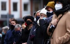 People wearing protective face masks stand as they pay their respects near the site where a car crashed into pedestrians in Trier, Germany, Dec 2, 2020. REUTERS