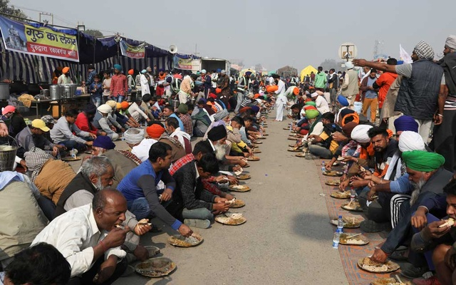 People serve food at a site of a protest against the newly passed farm bills at Singhu border near Delhi, India, Dec 1, 2020. REUTERS