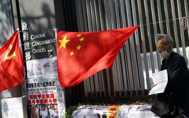 A pro-government supporter wearing a face mask holds a sign next to flags of Chinese Communist Party and China placed outside the Central Government Offices ahead of Hong Kong Chief Executive Carrie Lam's annual policy address at the Legislative Council in Hong Kong, China Nov 25, 2020. REUTERS