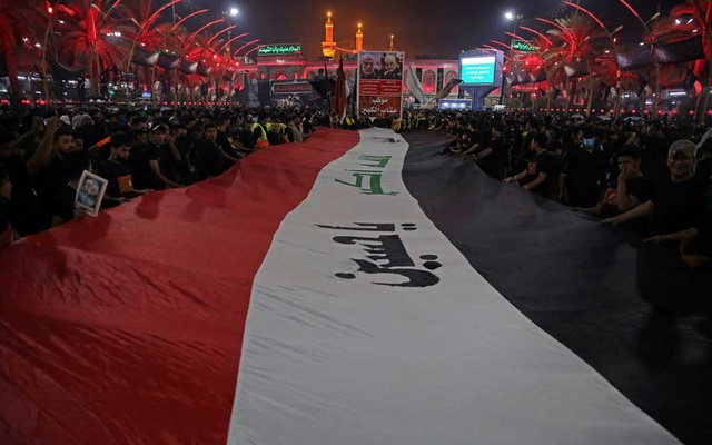 Pilgrims hold an Iraqi flag as they attend the ceremony of Shi'ite ritual of Arbaeen in Kerbala, Iraq, October 7, 2020. Picture taken October 7, 2020. Reuters