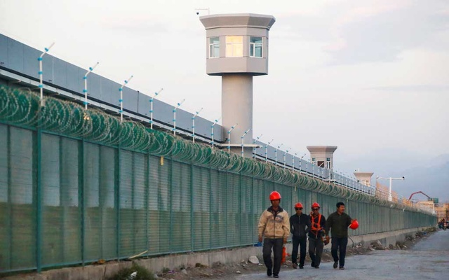 Workers walk by the perimeter fence of what is officially known as a vocational skills education centre in Dabancheng in Xinjiang Uighur Autonomous Region, China September 4, 2018. REUTERS