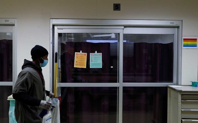 A housekeeper walks by the isolation room of a coronavirus disease (COVID-19) positive patient inside the emergency room bed at Roseland Community Hospital on the South Side of Chicago, Illinois, US, Dec 2, 2020. REUTERS
