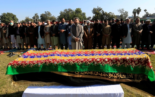 Afghan men pray near the coffin of journalist Malalai Maiwand, who was shot and killed by unknown gunmen in Jalalabad, Afghanistan December 10, 2020. REUTERS