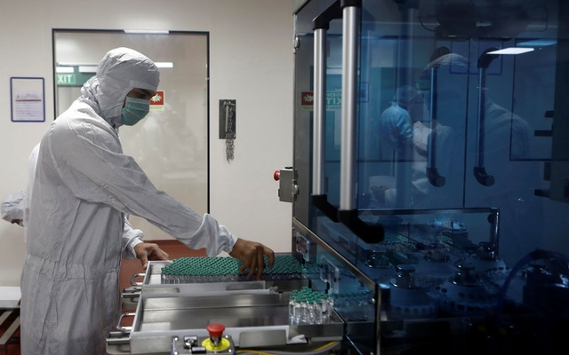 An employee in personal protective equipment (PPE) removes vials of AstraZeneca's COVISHIELD, coronavirus disease (COVID-19) vaccine from a visual inspection machine inside a lab at Serum Institute of India, in Pune, India, November 30, 2020. REUTERS