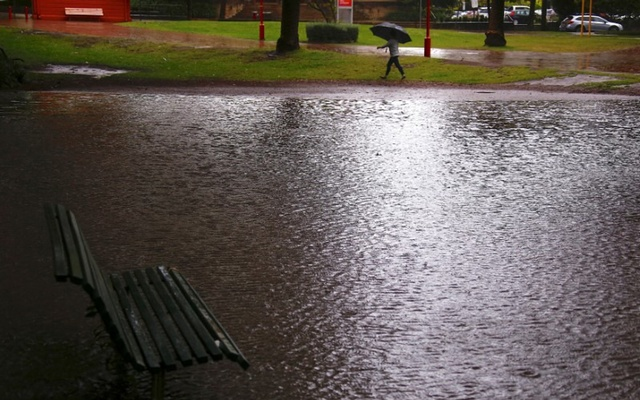 A woman carrying an umbrella walks past a flooded park as strong winds and floods cause traffic problems in Sydney, Australia, November 28, 2018. REUTERS