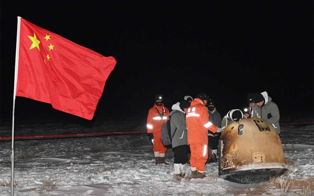 Researchers work around Chang'e-5 lunar return capsule carrying moon samples next to a Chinese national flag, after it landed in northern China's Inner Mongolia Autonomous Region, December 17, 2020. China Daily via REUTERS