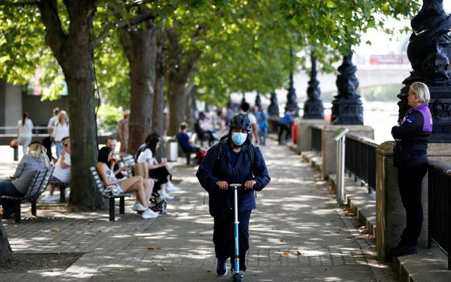 A woman wearing a protective face mask rides a scooter along the South Bank, amid the spread of coronavirus disease (COVID-19), in London, Britain, Aug 20, 2020. REUTERS
