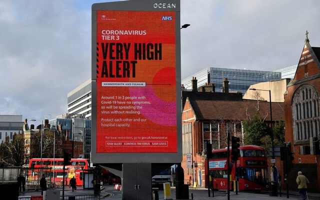 Pedestrians walk past a British government health information advertisement highlighting new restrictions amid the spread of the coronavirus disease (COVID-19), London, Britain, December 19, 2020. REUTERS