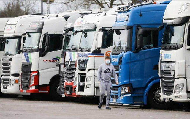 A driver wearing a face mask walks past lorries at Ashford International Truck Stop, as EU countries impose a travel ban from the UK following the coronavirus disease (COVID-19) outbreak, in Ashford, Britain December 22, 2020. REUTERS