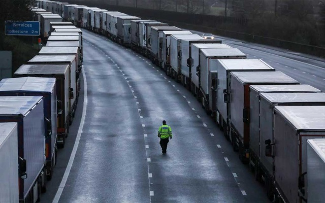 A man walks past lorries parked on the M20 motorway, as EU countries impose a travel ban from the UK following the coronavirus disease (COVID-19) outbreak, near Ashford, Britain, December 22, 2020. REUTERS