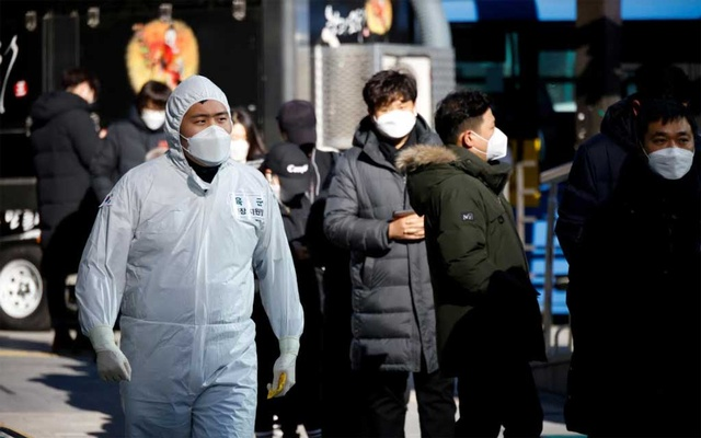 A South Korean soldier wearing a protective suit walks past people who wait in a line to undergo a coronavirus disease (COVID-19) test at a coronavirus testing site which is temporarily set up near a subway station in Seoul, South Korea, December 17, 2020. REUTERS