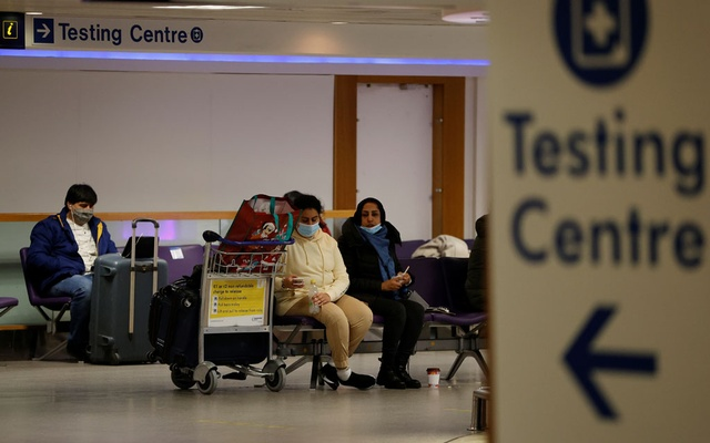 Passengers sit beneath a testing centre sign in the terminal building of Manchester Airport amid the outbreak of the coronavirus disease (COVID-19) in Manchester, Britain, December 3, 2020. Reuters