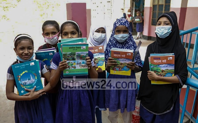 Students of Dholaipar Govt Primary School in Dhaka receive new textbooks on the first day of 2021.
