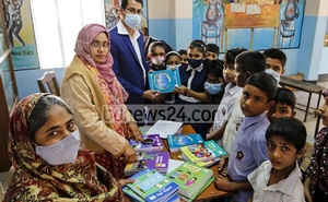 Teachers distribute new textbooks to students at Dholaipar Govt Primary School in Dhaka on the first day of 2021.