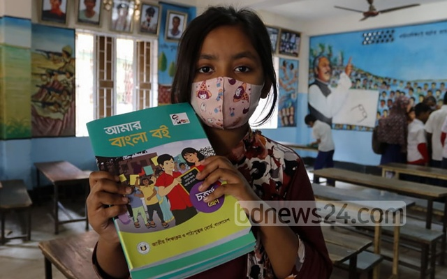 A fourth grader at Dholaipar Govt Primary School in Dhaka is happy after receiving new textbooks on the first day of the new year, Jan 1, 2021.