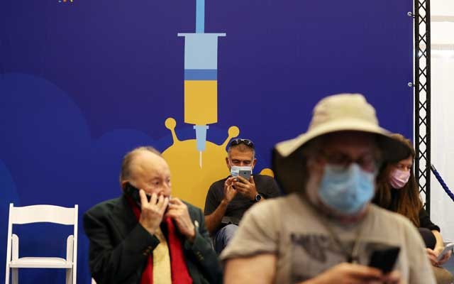 People wearing face masks wait at a new coronavirus disease (COVID-19) vaccination centre, as Israel continues its drive to vaccinate its elderly population against COVID-19, at Rabin Square in Tel Aviv, Israel Dec 31, 2020. REUTERS