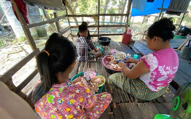 Burmese children help their parents peel crabs at their home in Ranong, Thailand on September 10, 2020. Reuters