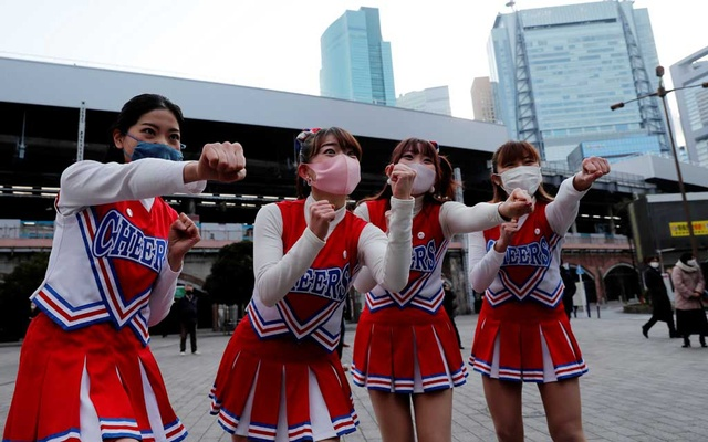 Cheerleaders wearing protective masks, amid the coronavirus disease (COVID-19) outbreak, practice before performing to cheer people up in front of Shimbashi Station during the commuting hour in Tokyo, Japan, January 7, 2021. REUTERS