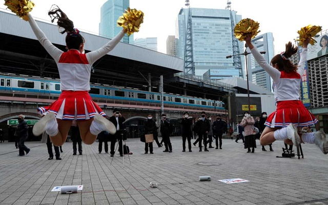 Cheerleaders wearing protective face shields, amid the coronavirus disease (COVID-19) outbreak, cheer people up in front of Shimbashi Station during the commuting hour in Tokyo, Japan, January 7, 2021. REUTERS