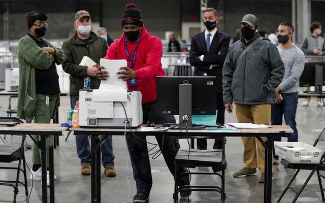 A Fulton County election worker puts absentee ballots in a scanner as election observers look on, at the Georgia World Congress Centre in Atlanta, Georgia, US, January 5, 2021. REUTERS