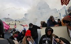 Supporters of US President Donald Trump cover their faces to protect from tear gas during a clash with police officers in front of the US Capitol Building in Washington, US, Jan 6, 2021. REUTERS