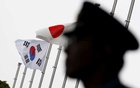 A police officer stands guard near Japan and South Korean national flags at a hotel. (Toru Hanai/Reuters)