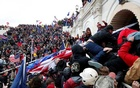 2021 - Hundreds of pro-Trump supporters stormed the Capitol and occupied the building for hours, ransacking offices, forcing an evacuation of lawmakers and interrupting their certification of the November presidential election. One woman in the mob was shot to death by police in a corridor, and one of several police officers injured in clashes with protesters died. Three more died of medical emergencies on the grounds during the tumult. REUTERS/Shannon Stapleton