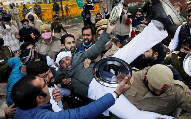 Police officers detain an activist of the youth wing of India's main opposition Congress party during a protest against new farm laws in New Delhi, India Jan 12, 2021. REUTERS