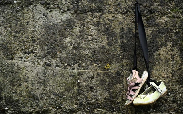 Baby shoes hang from a wall at the Tuam graveyard, where the bodies of 796 babies were uncovered at the site of a former Catholic home for unmarried mothers and their children on the day a government-ordered inquiry into former Church-run homes for unmarried mothers is formally published, in Tuam, Ireland, January 12, 2021. REUTERS