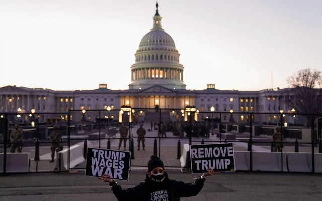 A protester holds signs near the US Capitol as the House of Representatives prepares to begin the voting process on a resolution demanding US Vice President Pence and the cabinet remove President Trump from office, in Washington, US, January 12, 2021. Reuters
