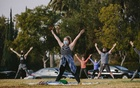 People wearing masks participate in a vinyasa yoga class on a lawn at the Hollywood Forever Cemetery in Los Angeles, Jan 3, 2021. The New York Times