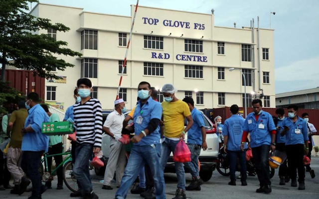Workers leave a Top Glove factory after their shifts in Klang, Malaysia, December 7, 2020. REUTERS