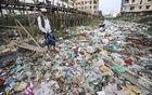 People use bamboo bridges to cross the garbage-filled Manda canal in Dhaka. Photo: Asif Mahmud Ove