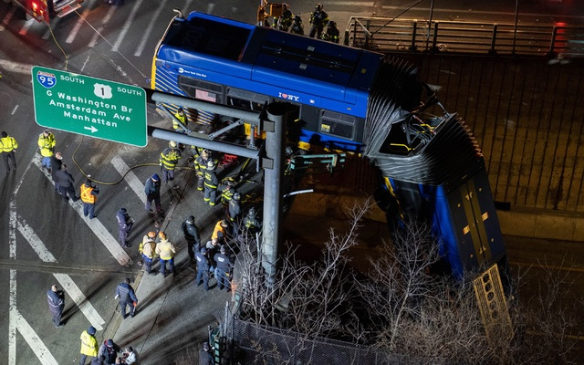 A tandem M.T.A. bus hangs over an overpass barrier in the Bronx early Friday morning, Jan. 15, 2021. The crashed happened Thursday night, causing the front portion to fall about 50 feet. The driver and at least six passengers were injured. (Dakota Santiago/The New York Times)