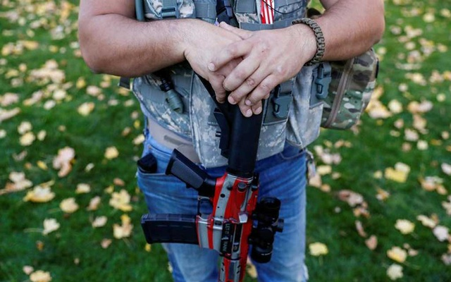 A member of Michigan Liberty Militia stands with a gun while supporters of US President Donald Trump rally outside the State Capitol building as votes continue to be counted following the 2020 US presidential election, in Lansing, Michigan, US, November 7, 2020. REUTERS