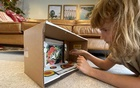 Ingrid Abbott, 11, with the butterfly museum she created out of a cardboard box. Exploring a passion at home can fill the void, say experts.The New York Times