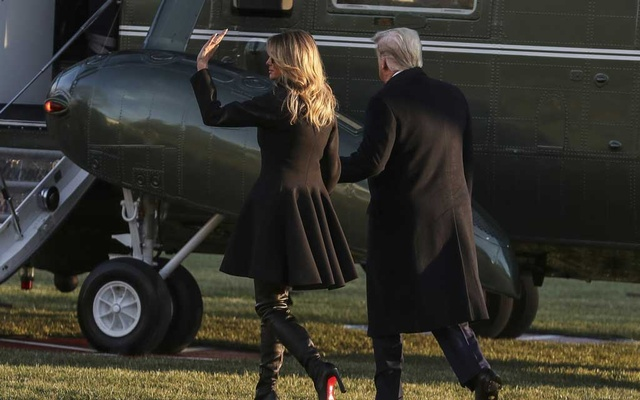 """FILE — President Donald Trump and first lady Melania Trump prepare to board Marine One, on their way to Mar-a-Lago, on the South Lawn of the White House in Washington, Dec 23, 2020. Few presidents have exploited the theatrical grandeur of the job quite as enthusiastically or as cynically as Donald Trump. As a group his family tapped into the dregs of """"Dynasty"""" and """"The Bonfire of the Vanities"""" past that sits nestled in our lizard brains. (Oliver Contreras/The New York Times)"""