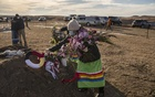 Carla Taken Alive, whose parents died of COVID-19, places flowers on their grave near Fort Yates, N.D., on Dec. 26, 2020. More than 400,000 people in the United States who had the coronavirus have died, according to data compiled by The New York Times on Tuesday Jan. 19, 2021, as the anniversary of the country's first known death in the pandemic approaches. (Victor J. Blue/The New York Times)