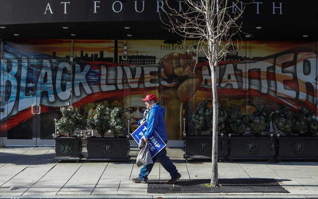 A supporter of outgoing President Donald Trump walks by a Black Lives Matter and George Floyd mural during US President Joe Biden's inauguration, in Washington D.C., US January 20, 2021. Reuters